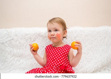 cute little girl a child with eczema or an allergy on her cheeks because of consuming citrus fruits, sits on a sofa with tangerines