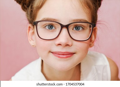 Cute little girl child preteen in eyeglasses education, school and vision concept isolated on a pink closeup