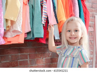 Cute little girl choosing clothes in dressing room