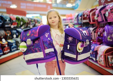 Cute little girl choosing a schoolbag before starting classes. Adorable pupil buying school backpack in a store. Back to school concept.