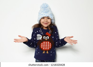 Cute little girl in Christmas sweater and knitted hat on white background