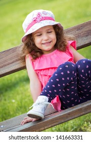 Cute little girl with closed eyes sitting on the bench in a park. Outdoors