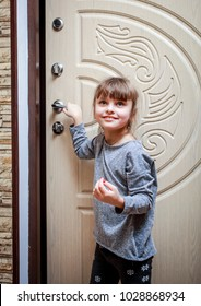 Cute little girl closes the door of his apartment.