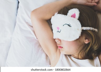 Cute little girl closeup sleeping in bed wearing white cat plush sleep mask. Early morning wake up, rise to kindergarten, school. Putting kid to sleep. Mom's correct daily routine, rest for child.