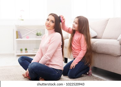 Cute little girl is combing her mother's hair sitting in the bedroom. Mothers Day, relationship, motherhood, joint activities and interests, trust, support, caress, maternal warmth, caring concept