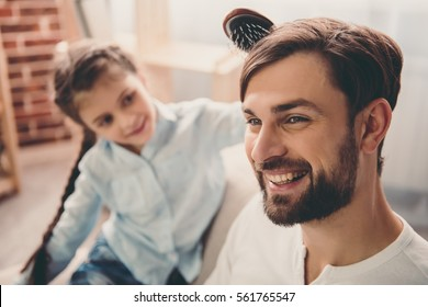 Cute little girl is combing her handsome father and smiling while they are playing together at home