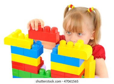 Cute little girl is constructing a house using colored building blocks