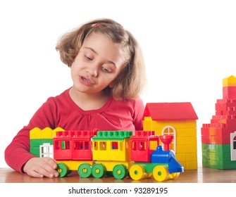 Cute little girl is constructing a house using building blocks