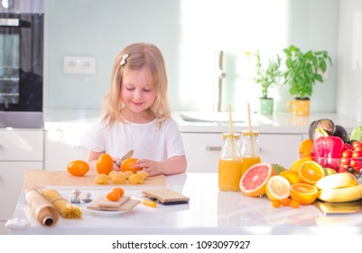 Cute little girl cooking and smiling in the kitchen at home.