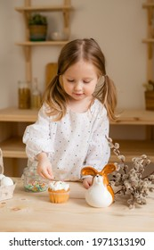 Cute little girl in a cotton dress at home in a wooden kitchen prepares an Easter cake