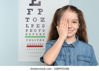 Cute little girl covering eye in ophthalmologist office