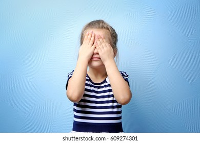 Cute little girl covering eyes with hands, on color background
