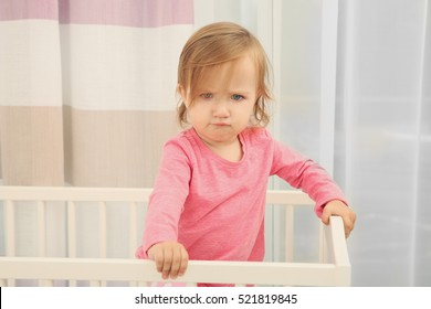 Cute little girl in cradle at baby room