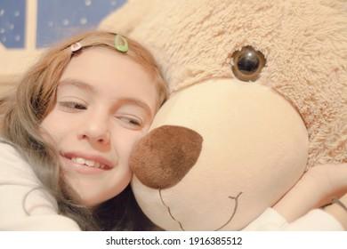 A cute little girl cuddling her big teddybear. Closeup shot.