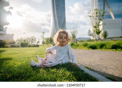 Cute little girl with curly blonde hair in beautiful white dress sitting on the green lawn in the city park near the skycrapers. Sunny day