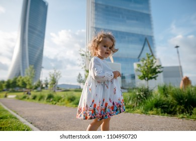 Cute little girl with curly blonde hair in beautiful white dress standing on the green lawn in the city park. Skycrapers background. Urban city. Sunny day