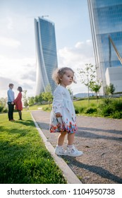 Cute little girl with curly blonde hair in beautiful white dress standing on the pathway in the city park. Parents and skycrapers on the background. Urban city. Sunny day