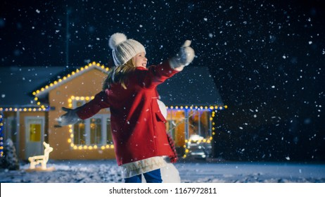 Cute Little Girl Dances and Playing. Child Enjoys Winter Weather. Having Fun One Winter Evening In the Background of the House with Lit Garlands and Christmas Tree and Snowman.