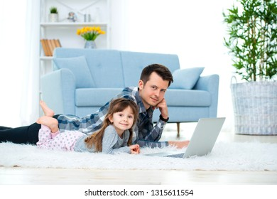 Cute little girl, daughter, sister and young dad father or brother look at the laptop monitor computer, lying on carpet on the floor in living room
