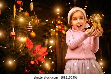 Cute little girl decorates Christmas tree at home and rejoices. Merry Christmas and Happy New Year!