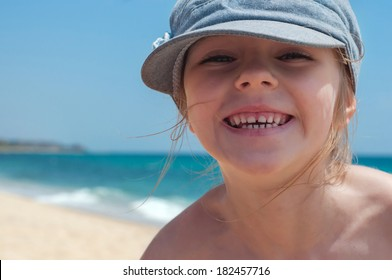 Cute little girl in denim cap on the beach