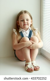 Cute little girl in denim shorts sits on the sill of the window, hugging her knees. Natural light from window