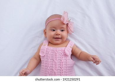 A cute little girl with a diadem on her head and a knitted pink bodysuit lies in bed close-up. Looks into the camera.