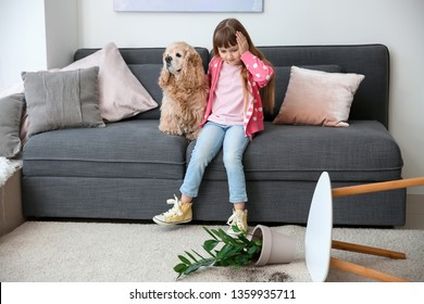 Cute little girl with dog and dropped houseplant on carpet