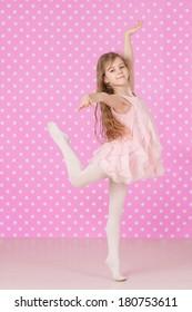 Cute  little girl doing ballet  exercises on pink background