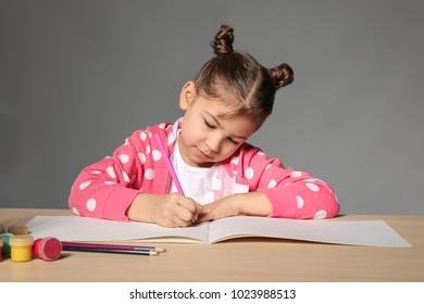 Cute little girl doing homework against grey background
