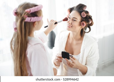 Cute little girl doing makeup to her attractive mom. Young beautiful mother and little daughter while applying makeup. Nice cozy bedroom. Daughter helping mother to use brush for makeup