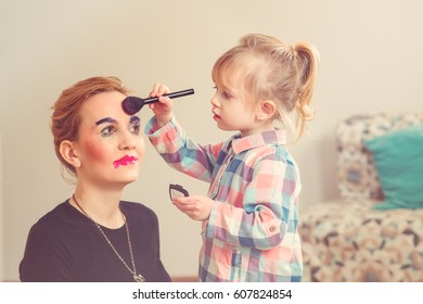 Cute little girl is doing makeup for her beautiful mother. Toned photo