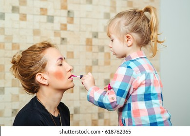 Cute little girl are doing makeup for her a beautiful mother.