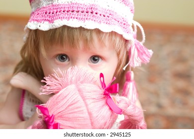 cute little girl with doll in her hands looking into the camera