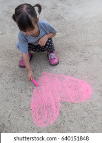 Cute little girl drawing with chalk outdoors, summer time (chalk)