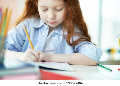 Cute little girl drawing with colorful crayons