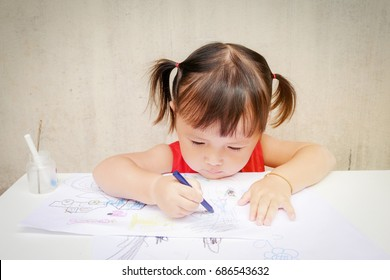 Cute little girl is drawing with crayon in preschool ,unlimited boundless imagination through Colorful :children development concept.