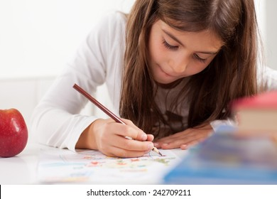 Cute little girl drawing. Elementary age.