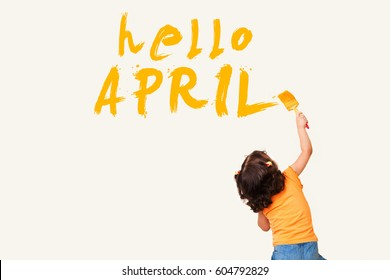 Cute little girl drawing : hello APRIL with painting brush on wall background