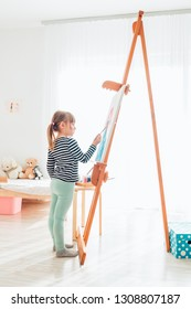 Cute Little girl drawing at home using eastel stand