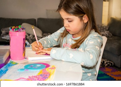 Cute little girl drawing at home. Home education.