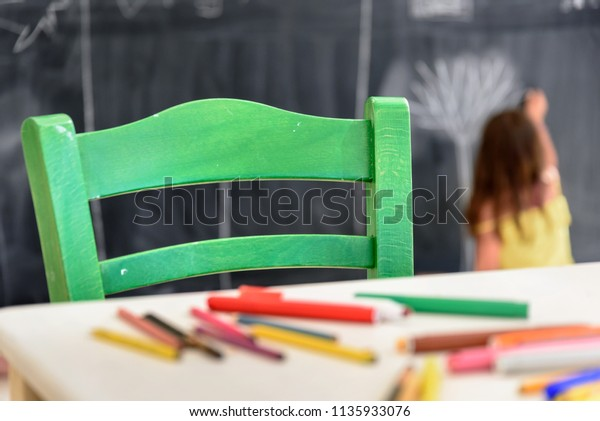 Cute little girl drawing and painting with chalk at kindergarten