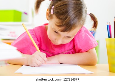 Cute little girl drawing with pencils at home