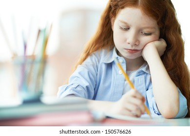 Cute little girl drawing with pencils at lesson