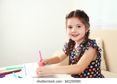 Cute little girl drawing picture on home interior background