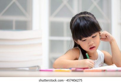 Cute little girl drawing picture using her imagination on home interior background