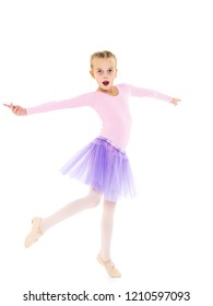 Cute little girl dreams of becoming a ballerina. The girl in the tutu is dancing in the room while she is studying ballet. Isolated on white background.