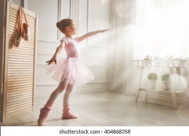 Cute little girl dreams of becoming a ballerina. Child girl in a pink tutu dancing in a room. Baby girl is studying ballet.