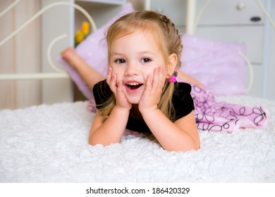 Cute little girl in dress on the bed laughing