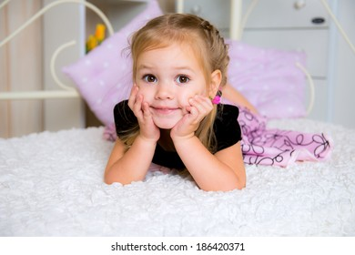 Cute little girl in dress on the bed in the room